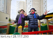 Купить «Boy teenager and man football fans with elk horns pose near residential buildings», фото № 28117293, снято 23 октября 2016 г. (c) Losevsky Pavel / Фотобанк Лори
