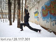 Купить «Man does exercises next to concrete wall with graffiti at winter», фото № 28117301, снято 29 февраля 2016 г. (c) Losevsky Pavel / Фотобанк Лори