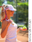 Купить «Happy girl in cap stands with racket on court at sunny summer day», фото № 28117321, снято 24 июня 2016 г. (c) Losevsky Pavel / Фотобанк Лори