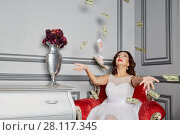 Купить «Woman in white dress sits in armchair at room under money banknotes shower», фото № 28117345, снято 14 ноября 2015 г. (c) Losevsky Pavel / Фотобанк Лори