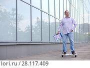 Купить «Man with folder rides GyroScooter near glass building at sunny summer day», фото № 28117409, снято 25 июня 2016 г. (c) Losevsky Pavel / Фотобанк Лори