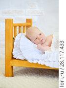 Купить «Beautiful baby lies in wooden small bed with white plaid in studio», фото № 28117433, снято 27 августа 2016 г. (c) Losevsky Pavel / Фотобанк Лори