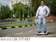 Купить «Happy man with documents rides GyroScooter on street at sunny summer day», фото № 28117437, снято 25 июня 2016 г. (c) Losevsky Pavel / Фотобанк Лори
