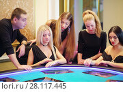 Купить «Four women and man play in casino with electronic table, focus on two on left», фото № 28117445, снято 24 октября 2016 г. (c) Losevsky Pavel / Фотобанк Лори