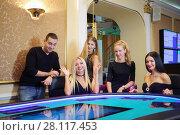 Купить «Four beautiful women and man play poker in casino with electronic table», фото № 28117453, снято 24 октября 2016 г. (c) Losevsky Pavel / Фотобанк Лори