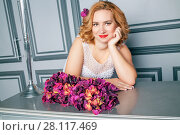 Купить «Smiling blonde woman sits at table with bunch of flowers», фото № 28117469, снято 14 ноября 2015 г. (c) Losevsky Pavel / Фотобанк Лори