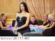 Купить «Pretty woman in black dress sits on table in casino, four people play poker out of focus», фото № 28117481, снято 24 октября 2016 г. (c) Losevsky Pavel / Фотобанк Лори