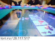 Купить «Electronic table in modern casino and hands of four players out of focus», фото № 28117517, снято 24 октября 2016 г. (c) Losevsky Pavel / Фотобанк Лори