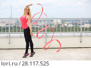 Купить «Happy beautiful blonde with red curly ribbon standing on tiptoe on the roof of a multistory building», фото № 28117525, снято 30 июля 2015 г. (c) Losevsky Pavel / Фотобанк Лори