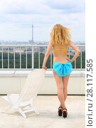 Купить «The girl in a blue bikini with a bow on the buttocks is nearly white beach chairs on the roof of a multistory building, view from the back», фото № 28117585, снято 30 июля 2015 г. (c) Losevsky Pavel / Фотобанк Лори