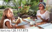 Купить «Mother and adorable little girl having breakfast at outdoor cafe», видеоролик № 28117873, снято 16 октября 2016 г. (c) Алексей Кузнецов / Фотобанк Лори