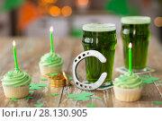 Купить «glasses of beer, cupcakes, horseshoe and coins», фото № 28130905, снято 31 января 2018 г. (c) Syda Productions / Фотобанк Лори