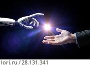 Купить «robot and human hand flash light over black», фото № 28131341, снято 6 сентября 2016 г. (c) Syda Productions / Фотобанк Лори