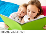 Купить «little girls or sisters reading book in bed», фото № 28131421, снято 15 октября 2017 г. (c) Syda Productions / Фотобанк Лори