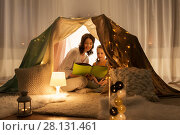 Купить «happy family reading book in kids tent at home», фото № 28131461, снято 27 января 2018 г. (c) Syda Productions / Фотобанк Лори