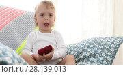 Купить «Kid using smartphone sitting in the chair alone», видеоролик № 28139013, снято 7 марта 2018 г. (c) Ekaterina Demidova / Фотобанк Лори