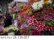 Купить «Женщина продает букеты весенних тюпанов на цветочном рынке в канун празднования Международного женского дня 8 Марта в городе Москве, Россия», фото № 28139057, снято 7 марта 2018 г. (c) Николай Винокуров / Фотобанк Лори