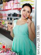 Купить «Positive girl in the shop taking candy in hands», фото № 28139181, снято 25 апреля 2017 г. (c) Яков Филимонов / Фотобанк Лори