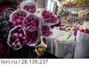 Купить «Женщина продает букеты весенних тюпанов на цветочном рынке в канун празднования Международного женского дня 8 Марта в городе Москве, Россия», фото № 28139237, снято 7 марта 2018 г. (c) Николай Винокуров / Фотобанк Лори