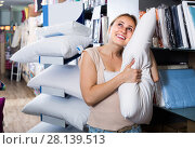Купить «portrait of female customer choosing pillow in bedding section in shop», фото № 28139513, снято 22 мая 2018 г. (c) Яков Филимонов / Фотобанк Лори
