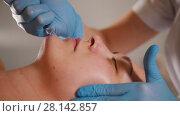 Купить «Cosmetologist massaging client's face in the beauty salon using a special cosmetic oil», видеоролик № 28142857, снято 16 августа 2018 г. (c) Константин Шишкин / Фотобанк Лори