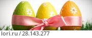 Купить «Three easter eggs wrapped in pink ribbon», фото № 28143277, снято 23 января 2019 г. (c) Wavebreak Media / Фотобанк Лори