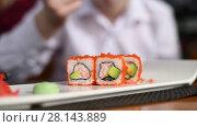 Купить «teenager eats rolls in restaurant», видеоролик № 28143889, снято 8 марта 2018 г. (c) Володина Ольга / Фотобанк Лори