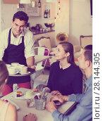 Купить «smiling waiter bringing ordered dishes to friends in tearoom», фото № 28144305, снято 5 июня 2017 г. (c) Яков Филимонов / Фотобанк Лори