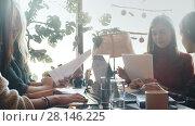 Купить «Working atmosphere, female colleagues working in cafe during lunch», видеоролик № 28146225, снято 30 января 2018 г. (c) Виктор Аллин / Фотобанк Лори
