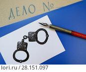 Папка с надписью «Дело №», нарисованные наручники и перо. Стоковое фото, фотограф ViktoriiaMur / Фотобанк Лори