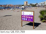 Информационный щит с правилами поведения на пляже Playa de Las Vistas в городе Los Cristianos. Атлантический океан, остров Тенерифе, Канары, Испания (2016 год). Редакционное фото, фотограф Кекяляйнен Андрей / Фотобанк Лори