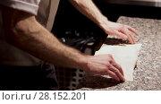 Купить «Chef seals the closed pizza and puts it to the oven using a culinary shovel», видеоролик № 28152201, снято 23 февраля 2018 г. (c) Ирина Мойсеева / Фотобанк Лори