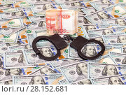 Купить «Steel police handcuffs lying on the background of american dollars with folded stack of banknotes of russian roubles», фото № 28152681, снято 4 января 2017 г. (c) FotograFF / Фотобанк Лори