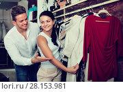 Купить «Young couple purchasing dress and blouse», фото № 28153981, снято 24 октября 2016 г. (c) Яков Филимонов / Фотобанк Лори