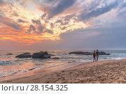 Купить «Молодая пара гуляет по песчаному тропическому пляжу на закате. Амбалангода, Шри-Ланка», фото № 28154325, снято 4 февраля 2018 г. (c) Владимир Сергеев / Фотобанк Лори