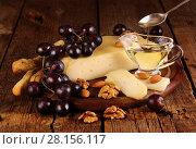 Купить «Сыр грюйер на деревянном столе с виноградом, орехами и оливковым маслом», фото № 28156117, снято 16 января 2019 г. (c) Марина Володько / Фотобанк Лори