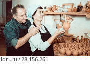 Купить «Couple among the pottery», фото № 28156261, снято 12 октября 2016 г. (c) Яков Филимонов / Фотобанк Лори