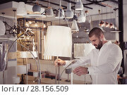 Купить «Man customer choosing floor lamp in furniture showroom», фото № 28156509, снято 29 января 2018 г. (c) Яков Филимонов / Фотобанк Лори