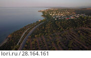 Купить «Flying over Trikorfo Beach coastline with cottages and green uplands, Greece», видеоролик № 28164161, снято 27 февраля 2018 г. (c) Данил Руденко / Фотобанк Лори