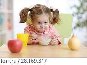 Купить «Cute little girl eating yogurt at home», фото № 28169317, снято 5 августа 2020 г. (c) Оксана Кузьмина / Фотобанк Лори