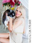 Купить «Pretty young blonde holds fluffy black rabbit on white bed in room», фото № 28170669, снято 20 ноября 2015 г. (c) Losevsky Pavel / Фотобанк Лори