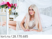 Купить «Pretty blonde poses on white bed with pillows in cozy bedroom», фото № 28170685, снято 20 ноября 2015 г. (c) Losevsky Pavel / Фотобанк Лори