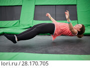 Купить «Young woman jumps on trampoline attraction in lying position», фото № 28170705, снято 29 августа 2016 г. (c) Losevsky Pavel / Фотобанк Лори