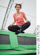 Купить «Young woman jumps on trampoline attraction in sitting position imitating levitation», фото № 28170713, снято 29 августа 2016 г. (c) Losevsky Pavel / Фотобанк Лори