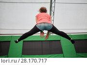 Купить «Young woman jumps on trampoline attraction making leg-split, rear view», фото № 28170717, снято 29 августа 2016 г. (c) Losevsky Pavel / Фотобанк Лори