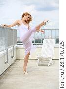 Купить «Beautiful girl in white leaning on railing lifted her leg up on the roof of a multistory building», фото № 28170725, снято 30 июля 2015 г. (c) Losevsky Pavel / Фотобанк Лори