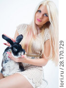 Купить «Blonde with long hairs sits on chair with funny rabbit in white studio», фото № 28170729, снято 20 ноября 2015 г. (c) Losevsky Pavel / Фотобанк Лори