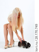 Купить «Blonde with long hairs sits on chair and touches black rabbit in white studio», фото № 28170749, снято 20 ноября 2015 г. (c) Losevsky Pavel / Фотобанк Лори