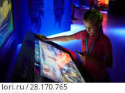 Купить «MOSCOW, RUSSIA - AUG 30, 2016: Girl (with model release) scroll text on interactive screen in history park Russia - My History in VDNKh. Museum presents key points of development of Russian state.», фото № 28170765, снято 30 августа 2016 г. (c) Losevsky Pavel / Фотобанк Лори
