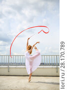 Купить «Beautiful gymnast in white with raised hands with red curly ribbon standing on a leg on the roof of a multistory building», фото № 28170789, снято 30 июля 2015 г. (c) Losevsky Pavel / Фотобанк Лори
